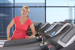 Portrait of smiling senior woman with water bottle on treadmill in health club Stock Photo