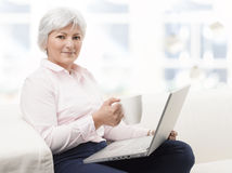 Smiling senior woman working on laptop. Portrait of a smiling senior woman working on laptop and drinking a cup of coffee Royalty Free Stock Photo