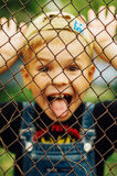 Portrait of smiling seven year old boy. Seven year old boy  with. Brown eyes and blond hair. Young boy in a black T-shirt and denim overalls outdoor.  Boy's Royalty Free Stock Photo