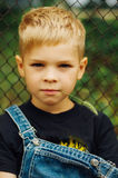 Portrait of smiling seven year old boy. Seven year old boy  with. Brown eyes and blond hair. Young boy in a black T-shirt and denim overalls outdoor.  Boy's Royalty Free Stock Image