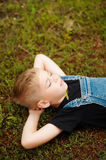 Portrait of smiling seven year old boy. Seven year old boy  with. Brown eyes and blond hair. Young boy in a black T-shirt and denim overalls outdoor.  Boy's Stock Photos