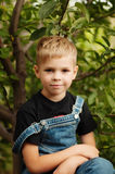 Portrait of smiling seven year old boy. Seven year old boy  with. Brown eyes and blond hair. Young boy in a black T-shirt and denim overalls outdoor.  Boy's Stock Images