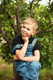 Portrait of smiling seven year old boy. Seven year old boy  with. Brown eyes and blond hair. Young boy in a black T-shirt and denim overalls outdoor.  Boy's Stock Image
