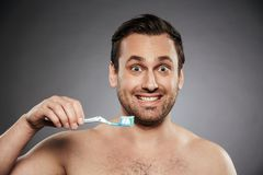 Portrait of a smiling shirtless man holding toothbrush. With a toothpaste isolated over gray background Stock Images