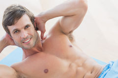 Portrait of a smiling shirtless young man doing sit ups Royalty Free Stock Photo
