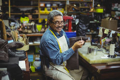 Portrait of smiling shoemaker applying glue on shoe Stock Images