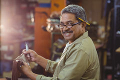 Portrait of smiling shoemaker cutting a piece of leather Stock Photography