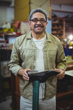 Portrait of smiling shoemaker examining a shoe. In workshop Royalty Free Stock Images