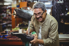 Portrait of smiling shoemaker hammering on a shoe Stock Photo