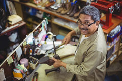 Portrait of smiling shoemaker hammering on a shoe. In workshop Stock Photography