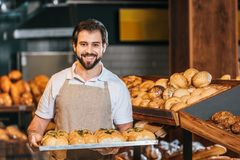 portrait of smiling shop assistant arranging fresh pastry royalty free stock photos