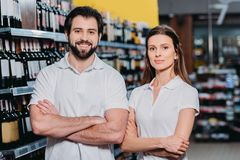 portrait of smiling shop assistants with arms crossed royalty free stock photos