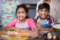 Portrait of smiling siblings with flour on face at home Royalty Free Stock Images