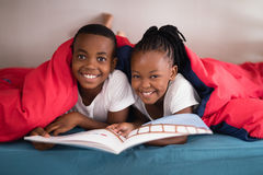 Portrait of smiling siblings holding book together on bed Royalty Free Stock Images