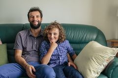 Smiling father and young son sitting together on their sofa stock photo