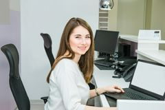 Portrait of smiling skilled administrative manager working on laptop with white empty screen in office satisfied with occupation,. Young female receptionist Stock Photo
