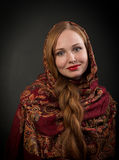 Portrait of smiling slavonic girl with red braided hair. Closeup portrait of smiling slavonic girl with red braided hair, looking at camera, on dark background Royalty Free Stock Images