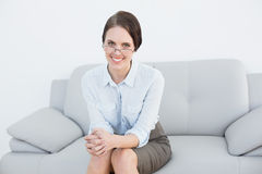 Portrait of a smiling smart woman sitting on sofa Royalty Free Stock Photography