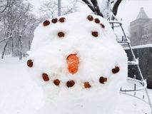 Portrait of a smiling snowman. Portrait of a smiling snowman with a carrot nose and eyes and a hazelnut flask, front view of a close-up face Royalty Free Stock Image