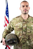 Portrait of smiling soldier standing with combat helmet. Against white background Royalty Free Stock Photos