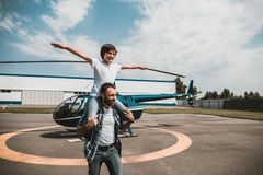 Beaming father having fun with cheerful kid. Portrait of smiling son playing with optimistic dad while sitting on his shoulders and gesticulating hands. He royalty free stock photo