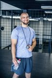 Portrait of a smiling sports coach with a bald head. l looks at the camera with stopwatch in hand. workout was successful. dressed royalty free stock photos