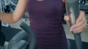 Portrait of smiling sportswoman on elliptical trainers in fitness club stock footage