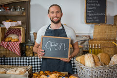 Portrait of smiling staff holding chalkboard with open sign at counter Royalty Free Stock Photo