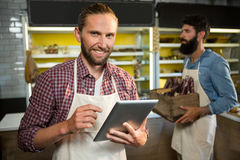 Portrait of smiling staff using digital tablet. In market Stock Photos
