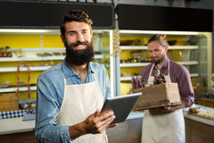 Portrait of smiling staff using digital tablet. In market Stock Photo