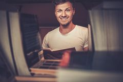 Portrait of a smiling student against bookshelf looking for a book at the  library. Royalty Free Stock Photography