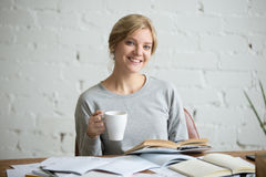 Portrait of smiling student girl at desk, mug in hand. Portrait of a smiling student girl sitting at the desk with a mug in her hand, education concept photo Royalty Free Stock Photos