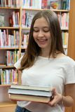 Happy teenage girl posing in the school library. Portrait of a smiling student girl standing holding books in the school library stock photography