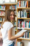 Happy teenage girl posing in the school library. Portrait of a smiling student girl standing holding books in the school library stock photos