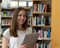 Happy teenage girl posing in the school library. Portrait of a smiling student girl standing holding books in the school library royalty free stock photo