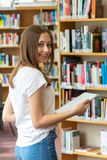 Happy teenage girl posing in the school library. Portrait of a smiling student girl standing holding books in the school library royalty free stock image