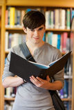 Portrait of a smiling student holding a binder. While looking at the camera Stock Photos