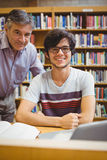 Portrait of smiling student with professor. In college library Stock Images