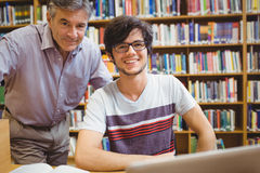 Portrait of smiling student with professor. In college library Royalty Free Stock Photos