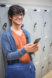 Portrait of smiling student using mobile phone in locker room Royalty Free Stock Images