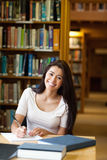 Portrait of a smiling student writing a paper Royalty Free Stock Images