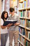 Portrait of smiling students reading a book. In a library Stock Photos