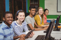 Portrait of smiling students studying in computer classroom Stock Images