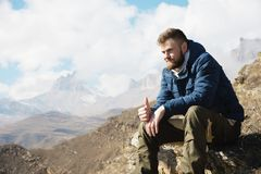 Portrait of a smiling stylish bearded hipster sitting on a rock on a mountainside in the background of an epic landscape. Sits and shows the gesture of a thumb Royalty Free Stock Photo