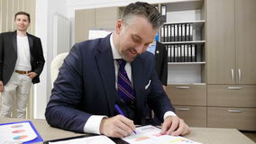 Portrait of smiling successful businessman working in his busy office with his two colleagues in the background. Portrait of successful smiling businessman stock video footage