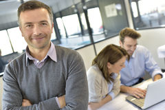 Portrait of a smiling and successful businessman with a workteam Stock Images