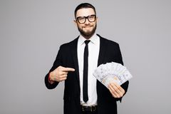 Portrait of a smiling successful man in suit and eyewear pointing finger at a bunch of money banknotes isolated over gray backgrou. Portrait of a smiling Stock Photo