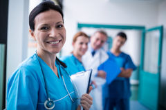 Portrait of smiling surgeon holding a clipboard in corridor. At hospital Royalty Free Stock Images