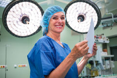 Portrait of smiling surgeon holding report in operation room Royalty Free Stock Images