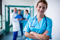 Portrait of smiling surgeon standing with arms crossed in corridor. At hospital Stock Photo